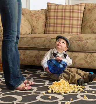 A little boy sitting and some Popcorn has been fallen down in Carpet